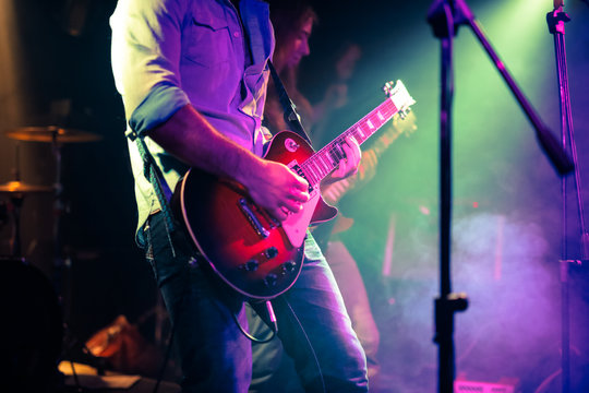 guitarist playing electrical guitar on a rock concert