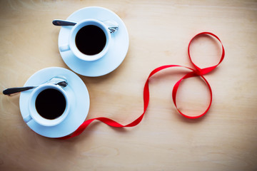 Couple cups with coffee, decorated by ribbon on wooden table.