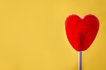 Red lollipop with heart shape on yellow background. Love concept. Valentine's Day.