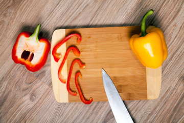 Cutting board whit three peppers. Home paprika and knife whit wood table background in kitchen.