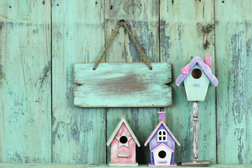 Blank wood sign hanging over birdhouses