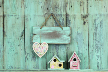 Blank wood sign with heart hanging over colorful birdhouses