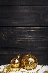 Two golden Christmas balls on black background