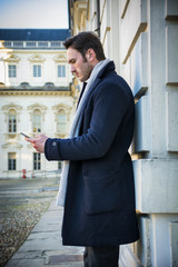 Handsome trendy man wearing dark coat standing and looking down at a cell phone that he is holding, outdoor in European city setting with elegant old historic building behind
