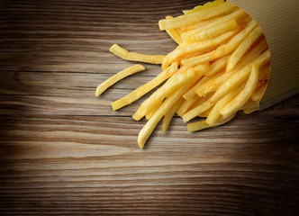 French fries in a paper basket on wooden background