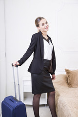 Beautiful blue eyes blonde woman with her suitcase in the hotel room. Business woman in hotel room.