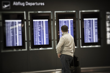 Unrecognizable person looking at Departures board in an airport