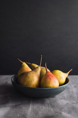 Bowl of ripe pears on table