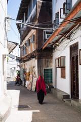 A woman wearing a Hijab walks through the alleyways of Stone Town, Zanzibar