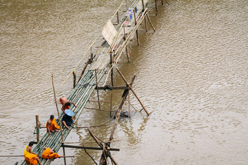 Men building a footbridge out of bamboo over the Mekong River