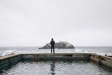 A man looks out onto the Pacific from the Sutro Baths in San Francisco, CA
