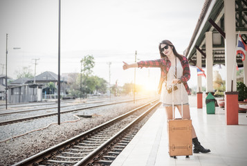 Hipster girl waiting train with leather vintage bag