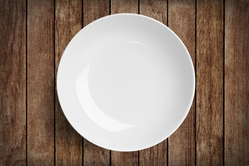 Simple white circular porcelain plate on wood with clipping path