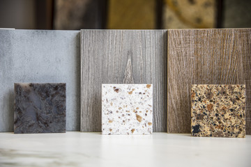 Three different granite countertop color samples standing close to three smales of kitchen doors or kitchen hardwood floor texture. Background is blury with countertop tiles