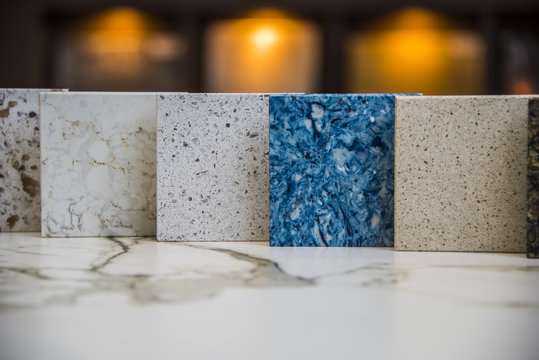 five square samples of kitchen countertops white brown, blue, white gray, withe with grans on kitchen countertops surface of marble stone. Background blurry with three lights.