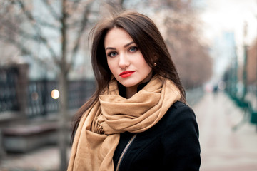 Autumn fashionable portrait of young happy brunette girl red lipstick outdoors in the city