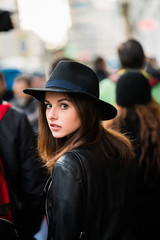 Young woman looking back in crowd