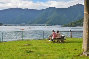 Back of couple sitting in the park looking at Kawaguchiko lake,
