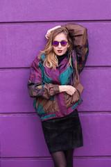 Trendy woman on purple wall