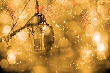 Microphone setting ready for DJ in celebration party.Fireworks blowing up in the sky with golden bokeh  in front of microphone ,season greeting.