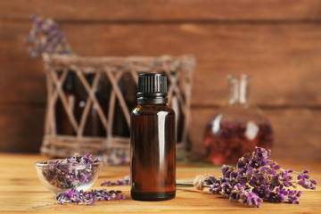 Bottle of lavender oil and flowers on wooden background
