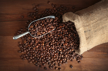 Coffee beans with scoop on table, top view