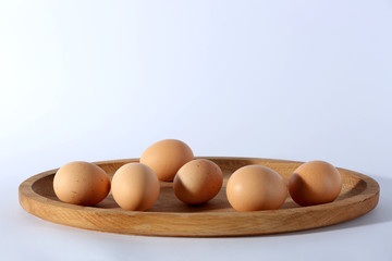 Raw eggs on tray on white background