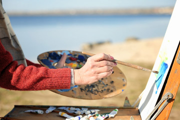 Senior female artist painting picture near river, close up