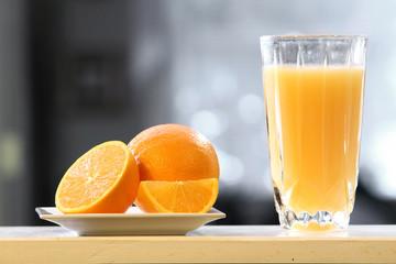 Orange juice on counter with fresh oranges