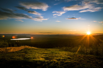 A beautiful landscape with a midnight sun above arctic circle. Dreamy scenery with light flares