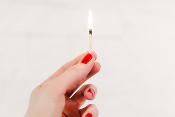 woman's hand holding a lighted match