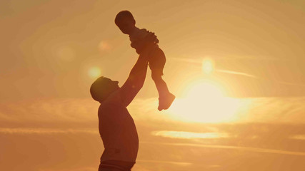 father and son silhouettes play at sunset beach. Happy family