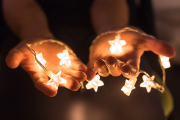 Hands holding shiny Christmas lights with star shapes