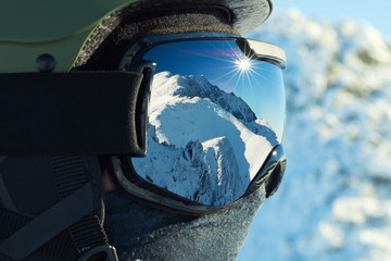 Close up shot of ski goggles with reflection of snowed mountains in it