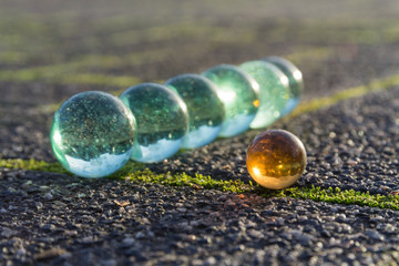 Translucent glass marbles on the sidewalk.