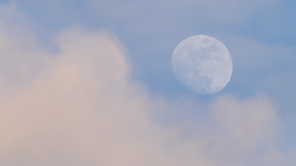 Moon and clouds in late afternoon light