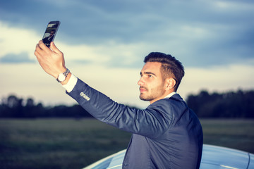 Portrait of young attractiave man in business suit using cell phone to take selfie photo outside his new stylish car outdoor in countryside