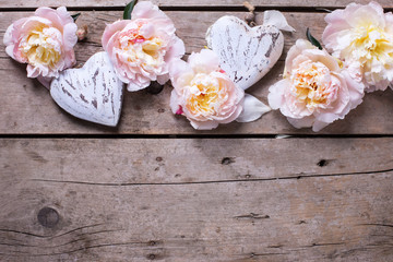 Border from decorative hearts and  pink peonies flowers on  wood