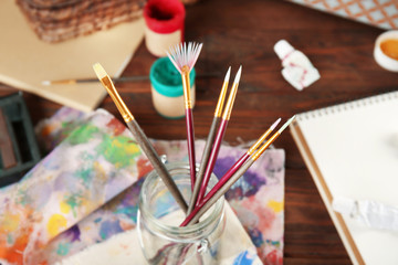 Brushes in a jar for craft on table