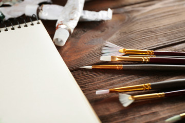 Brushes with album sheet on wooden background