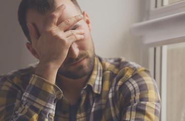 Handsome depressed man near window, closeup