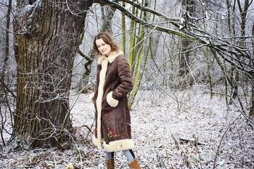 Girl walking in winter forest