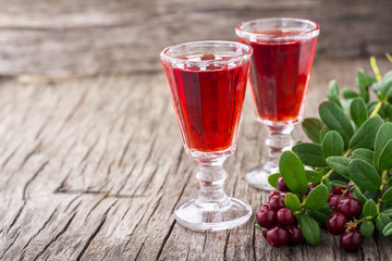 Sweet cranberry liqueur in two glasses on the background of ripe berries  a dark wooden . selective Focus