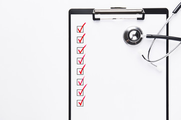 Stethoscope and clipboard with unfilled checklist, read check marks with copy space.