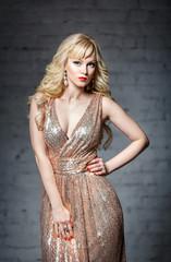 Beautiful blonde girl in a long gold dress