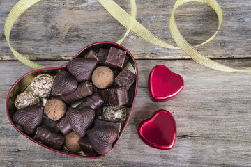 valentine's day concept/box shaped heart of chocolates on old wooden background