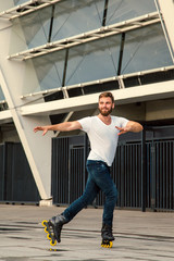 Bearded man on rollerblades standing in building background. Young fit man with white t-shirts and jeans on roller skates riding outdoors after rain.