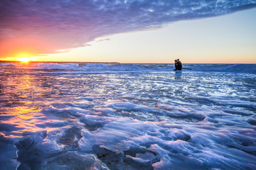Winter Adventure. A young photographer shooting a sunset on a frozen lake. Port Austin, Michigan.