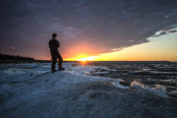 Male Photographer Standing On A Frozen Lake. Single male photographer standing on the edge of a frozen lake during a beautiful winter sunset. Port Crescent State Park. Port Austin, Michigan.