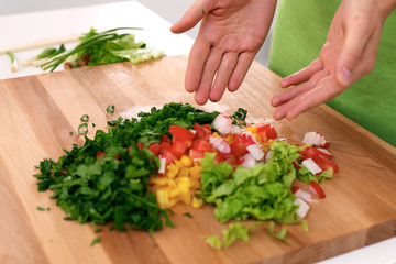Close up of  woman's hands cooking in the kitchen. Housewife offering ​​fresh salad. Vegetarian and healthily cooking concept